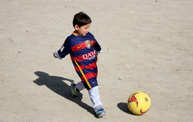 epa05181625 Five-year-old Afghan boy Murtaza Ahmadi, a young fan of FC Barcelona's Argentinian striker Lionel Messi, plays football wearing a FC Barcelona team jersey signed by Messi in Kabul, Afghanistan, 26 February 2016. Murtaza Ahmadi, who gained publicity after pictures emerged of him dressed in a striped plastic bag resembling Messi's national team jersey had his dream come true when he received a signed jersey and a ball from the Barcelona star on 25 February. The gifts were delivered to Murtaza Ahmadi in the central province of Ghazni by UNICEF.  EPA/HEDAYATULLAH AMID
