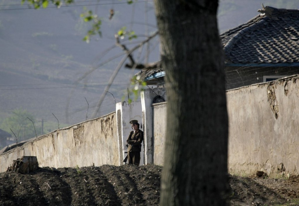 A female North Korean soldier stands guard at the entrance of a female prison on the banks of the Yalu River near the Chongsong county of North Korea opposite the Chinese border town of Hekou, northeastern China's Liaoning province, May 31, 2009. U.S. Defense Secretary Robert Gates said on Saturday the United States would not accept a nuclear-armed North Korea and he warned Pyongyang against transferring nuclear material overseas. REUTERS/Jason Lee (NORTH KOREA POLITICS MILITARY) - RTR243S8
