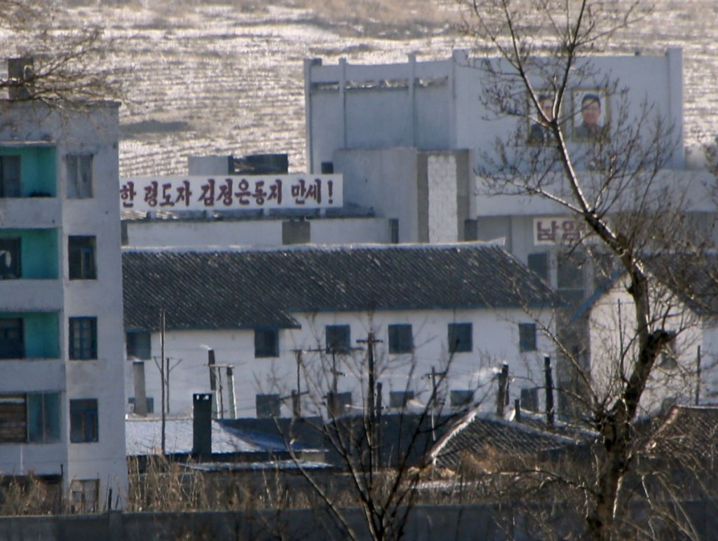 """A propaganda slogan and portraits of former North Korean leader Kim Jong Il (R) and his father and founder of North Korea Kim Il Sung (L) are seen in a North Korean village on the banks of the Tumen river, which is seen from the Chinese side in Tumen, China, January 7, 2016. The slogan reads,""""Hurrah, great leader Kim Jong Un"""". REUTERS/Kim Kyung-Hoon - RTX21D3S"""