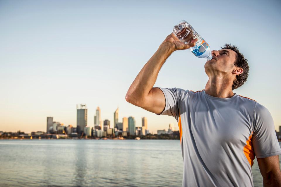 """Caucasian runner drinking water bottle near urban waterfront, Perth, Western Australia, Australia"""