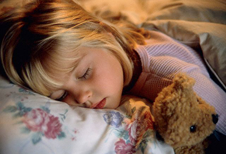 Girl Sleeping with Teddy Bear in Bed --- Image by © Roy Morsch/zefa/Corbis