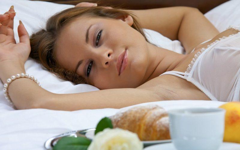 Девушка-улыбаясь-лежит-в-постели-800x500