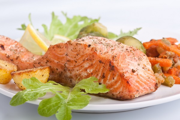 healthy salmon with vegetables on white plate