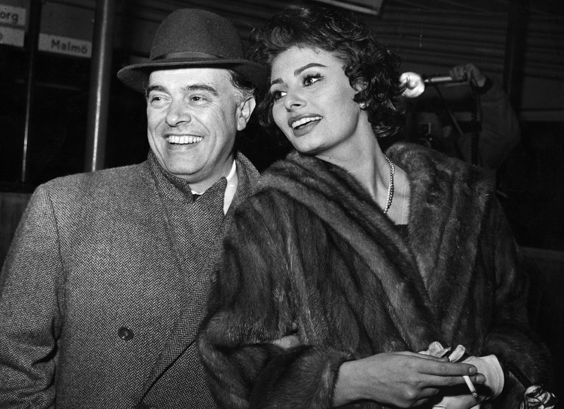 Carlo Ponti, the Italian film director and his wife Sophia Loren, the film actress arriving in Copenhagen en route from Rome to Los Angeles.They refused to comment on the rumour that Sophia was expecting a baby. (Photo by Keystone/Getty Images)